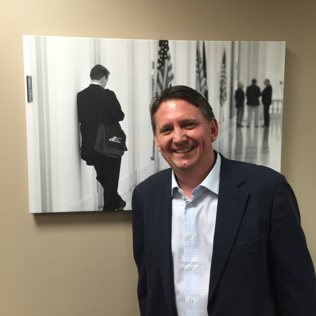 NCTC VP and General Counsel Jeff Nourse poses alongside his photo in ACA's new office.