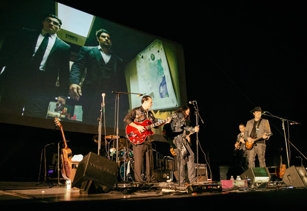 """Robert Rodriguez's band Chingon performs in front of a video montage of """"From Dusk Till Dawn: The Series"""" clips before a drive-in screening of the season two finale."""